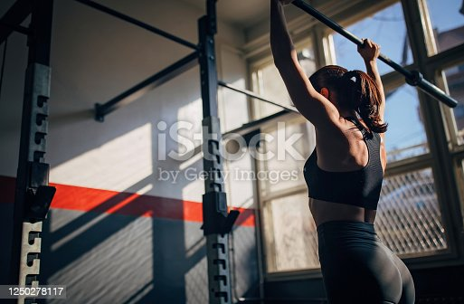 One fit young woman training alone in gym.