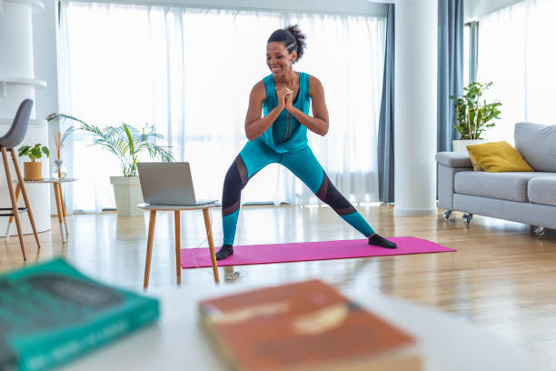 woman training indoors doing side lunges working out legs, hips and buttocks - exercise at home stock pictures, royalty-free photos & images