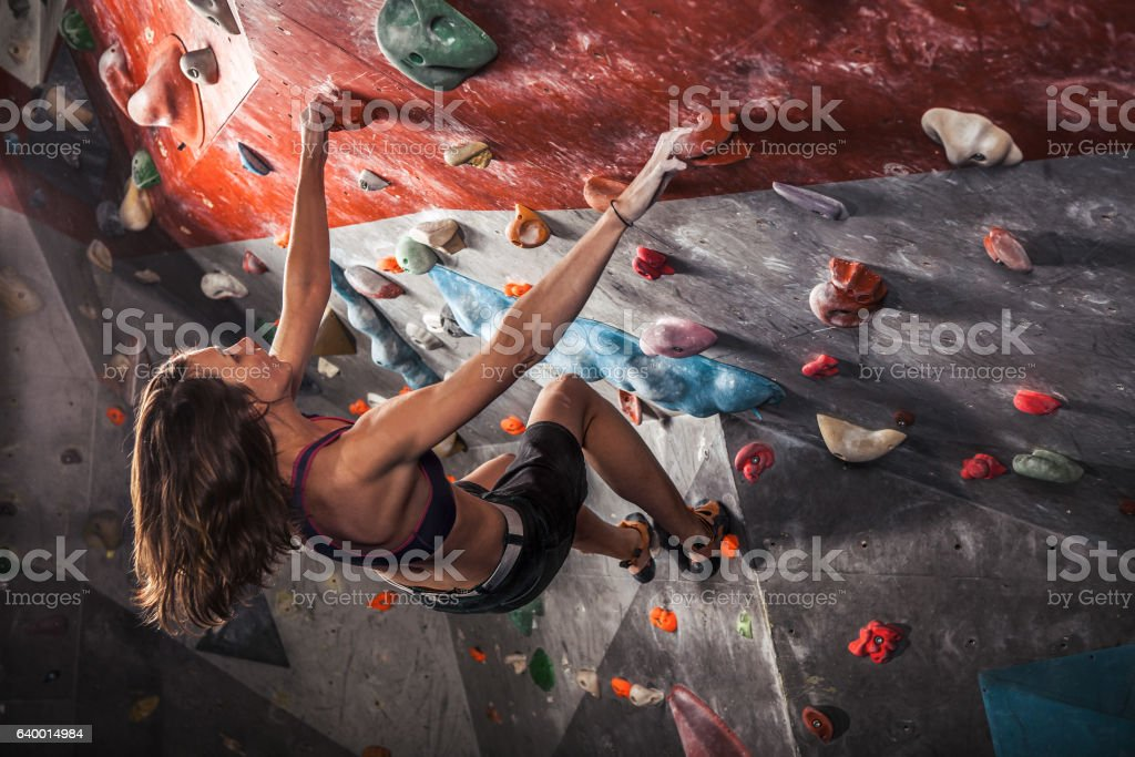 woman training on practice climbing wall indoor stock photo