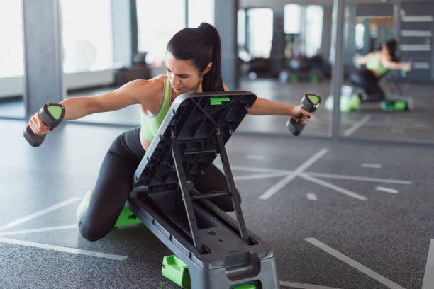 Woman training on step platform with dumbbells Adult muscular woman training on step platform doing lateral raises with dumbbells in gym lateral surface stock pictures, royalty-free photos & images