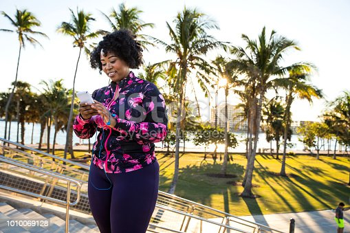 Curvy young black woman exercising, having sport training in Miami Beach public park