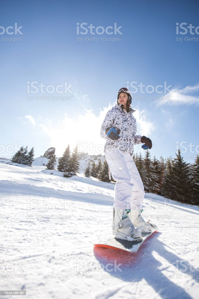 Young woman snowboarding on the top of the mountain