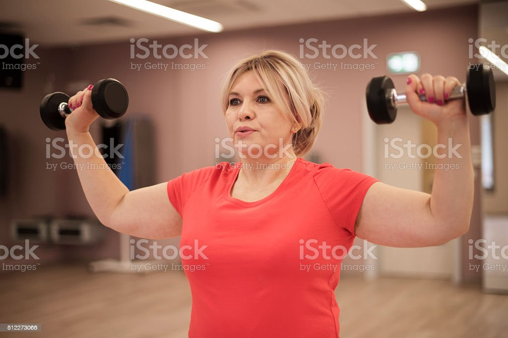 Woman training with dumbbells stock photo