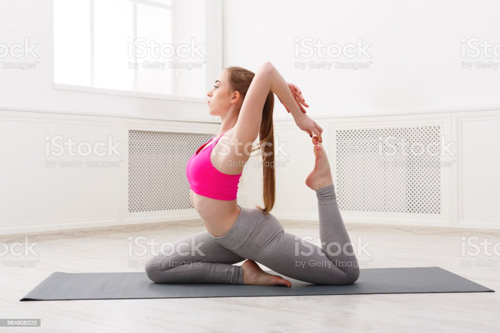 Woman training yoga in king pigeon pose. royalty-free stock photo