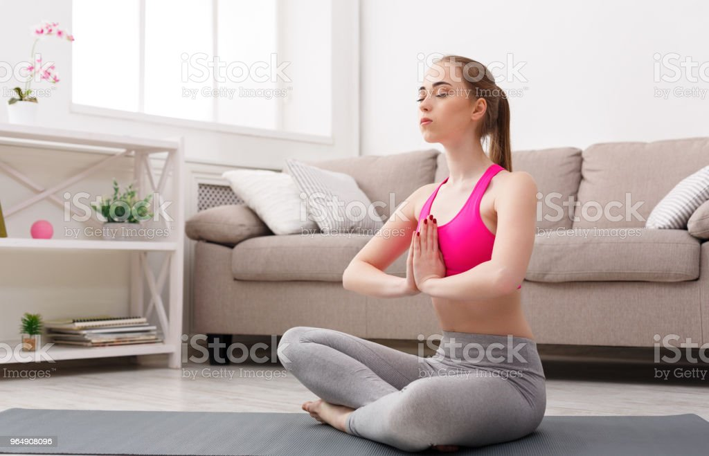 Woman training yoga in lotus pose royalty-free stock photo