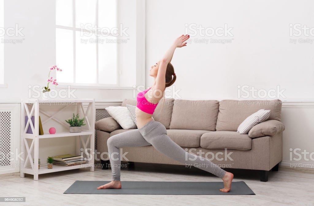 Woman training yoga in warrior pose royalty-free stock photo