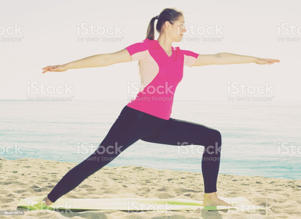 Woman training yoga poses on beach royalty-free stock photo