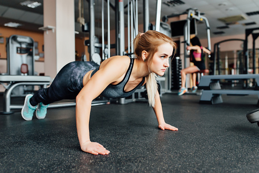 A woman trains in the gym performs plank exercise