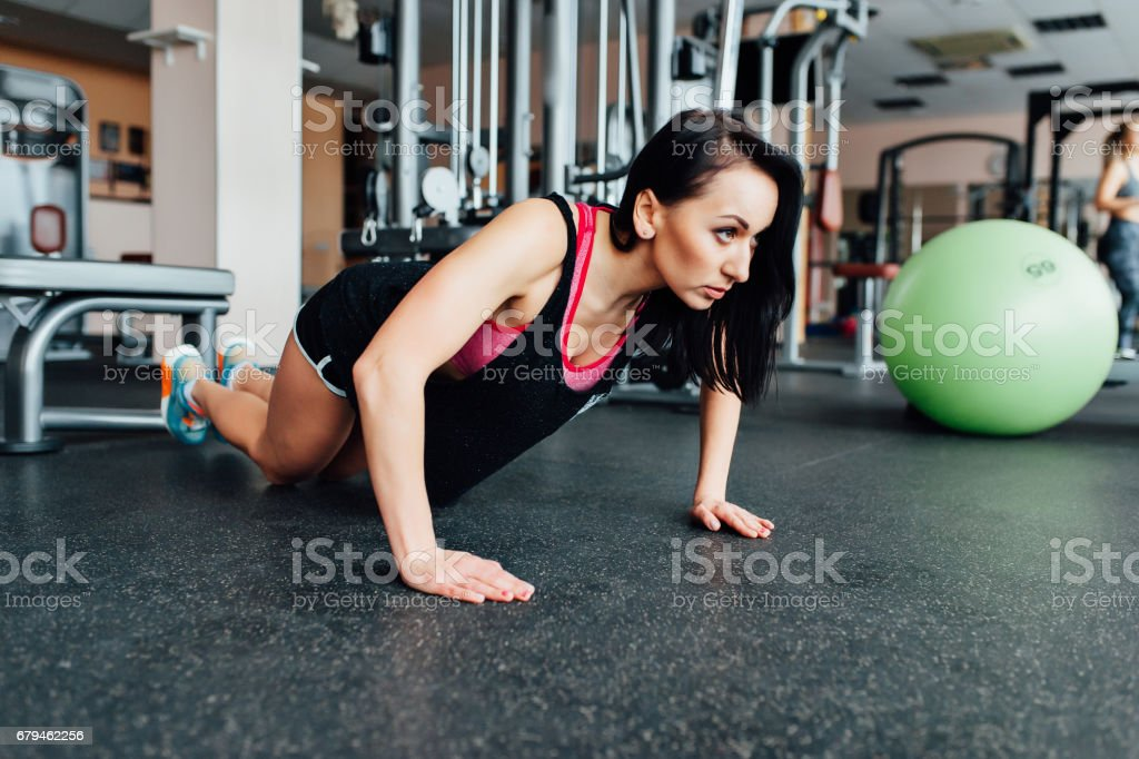 A woman trains in the gym performs plank exercise royalty-free stock photo