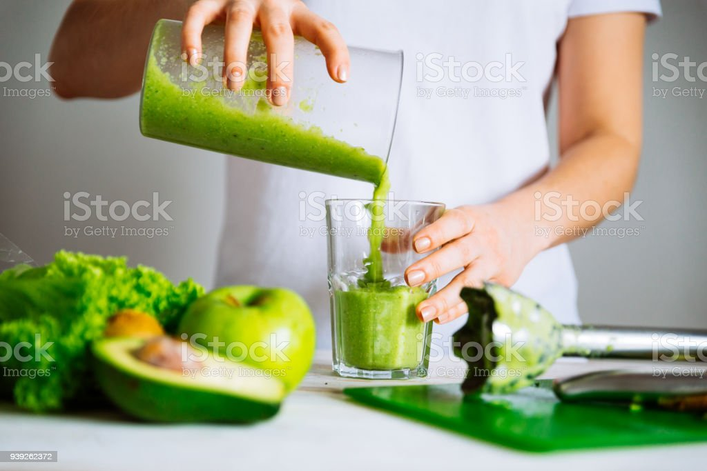 woman transfuse smoothie to glass. healthy food concept stock photo