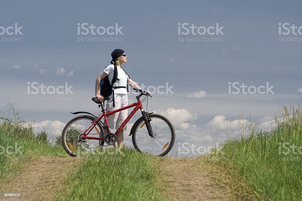 woman travel with bike on road in field royalty-free stock photo