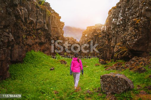 Woman traveler and explorer travels in the Icelandic landscape hiking across Iceland to discover unique nature in summer.