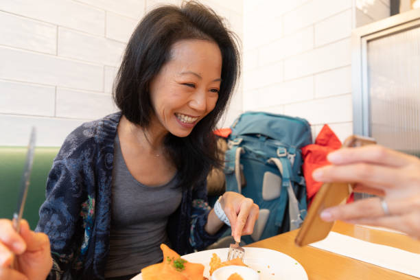 友人と食事を楽しむ女性旅行者 - showus ストックフォトと画像