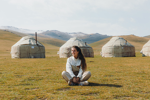 Young woman with long hair sitting at the meadow near the nomad yurts with mountain view in Tian Shan, Central Asia