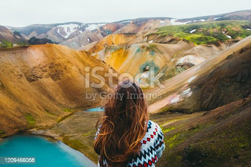 Young woman hiker with long hair and in a wool traditional Icelandic sweater got to the top of the mountain, relaxing looking at the beautiful multi-colored panoramic landscape with mountains and wild blue lakes in Landmannalaugar valley, Iceland
