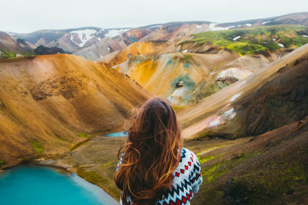 Woman traveler enjoying the view of scenic colorful rainbow mountains and turquoise lake in the wilderness stock photo