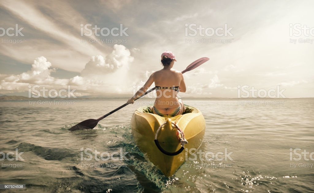 Woman traveler exploring calm tropical bay by kayak. stock photo