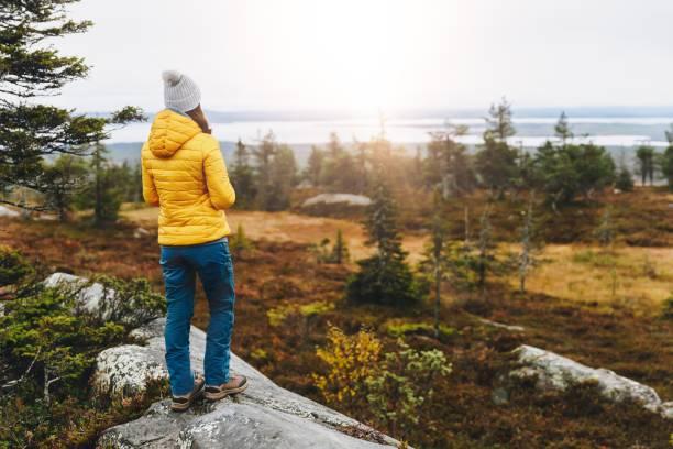 Frau Reisende in gelber Jacke von Rückenwanderung im Herbstwald in Finnland Lappland. – Foto