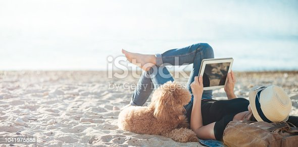 Woman traveler is holding touch pad, while is relaxing outdoors during his trip on the sea. Woman is traveling with her dog.