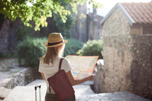 Woman traveler is looking at city map at town street in Europe. Girl tourist is searching apartment, student housing. Concept of travel, summer vacation, solo female tourism, adventure, trip, journey. stock photo