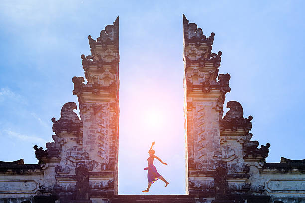 woman traveler jumping with energy in gate temple, bali, indonesia - インドネシア ストックフォトと画像