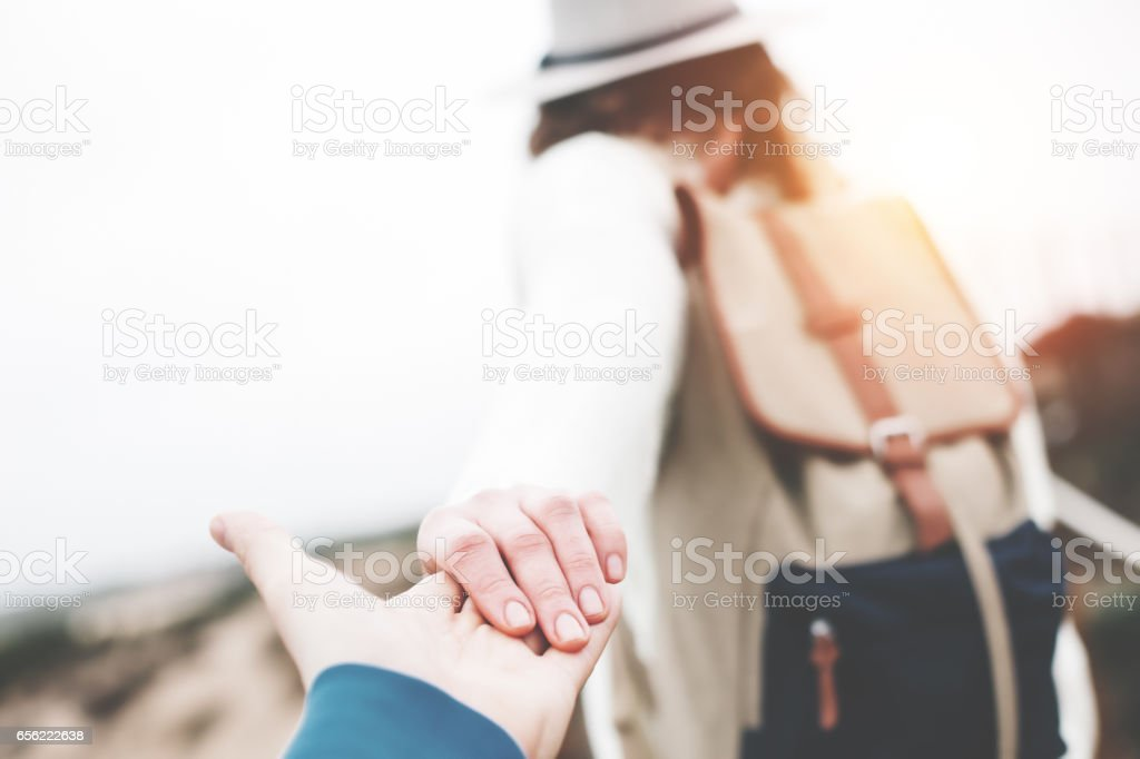 Woman traveler leading man by the hand stock photo