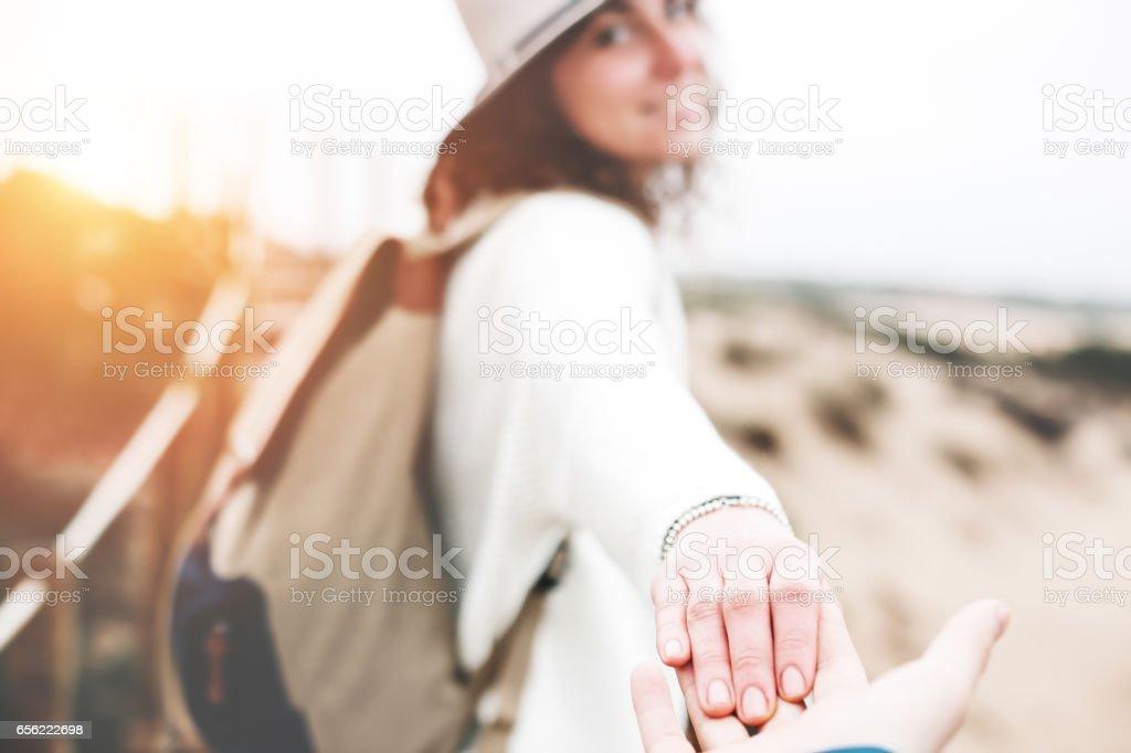 Woman traveler guiding man through the natural sand reserve, taking...