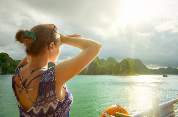 Woman traveler on the boat, enjoying view of the island at sunset stock photo