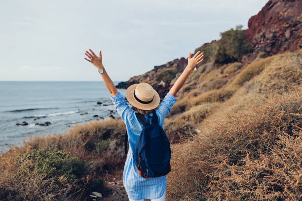 Woman traveler raised arms feeling happy on beach of Akrotiri, Santorini island, Greece in autumn. Tourism, traveling