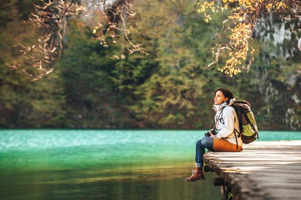 frau reisender sitzt auf holz brücke am bergsee am sonnigen herbsttag - nationalpark plitvicer seen stock-fotos und bilder