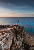 Woman traveler standing near sea on top of cliff in summer mountains and enjoying view of nature and sea. Cape Greco, Cyprus, Mediterranean Sea