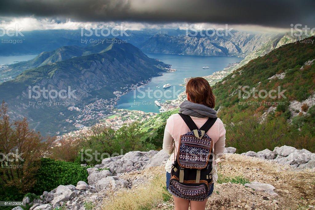 Woman traveler standing on mountain near sea bay stock photo