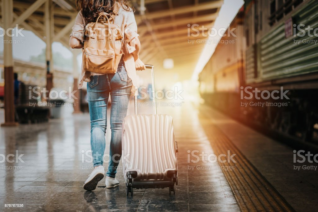 Woman traveler tourist walking with luggage to start her journey stock photo