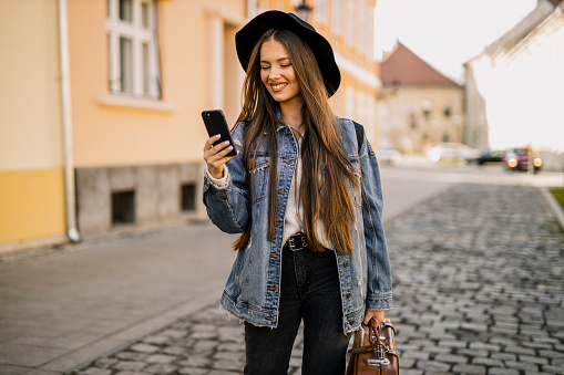 Woman traveler using her smart phone at the street
