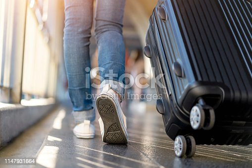 Woman traveler walking alone with suitcase bag. Travel weekend vacation trip.