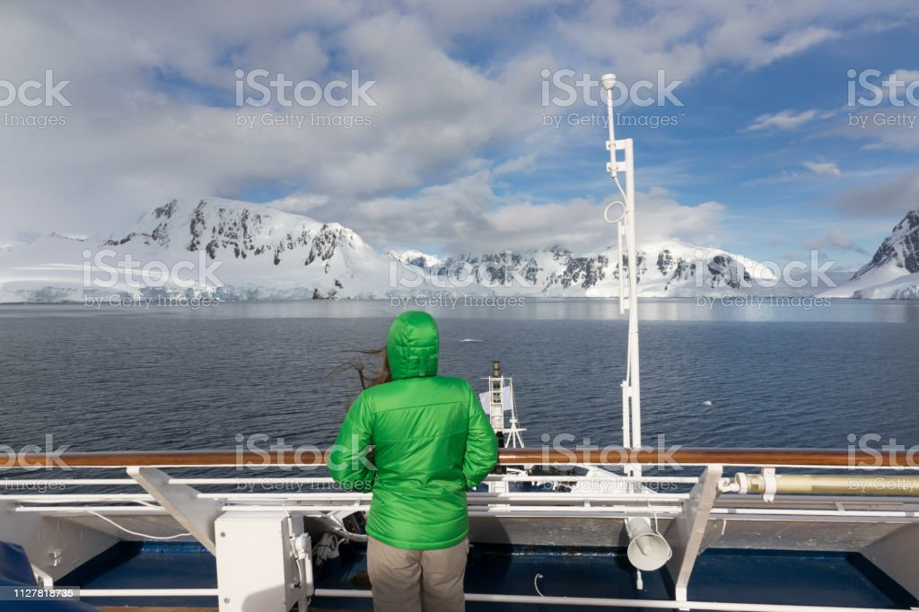 Woman traveler watches Neumeyer Channel Wiencke Island mountains Antarctica stock photo