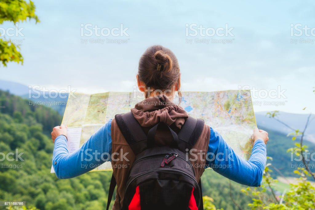 Woman traveler with backpack checks map to find directions in wilderness area, real explorer. Travel Concept - Royalty-free 20-29 Years Stock Photo