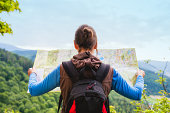 Hiking woman traveler with backpack checks map to find directions in wilderness area, real explorer. Travel Concept
