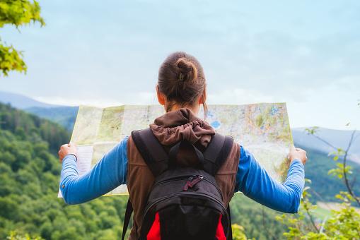婦女旅行者與背包檢查地圖找到方向在荒野地區 真正的探險家旅遊理念 照片檔及更多 20多歲 照片