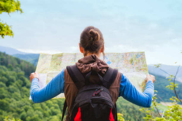 Woman traveler with backpack checks map to find directions in wilderness area, real explorer. Travel Concept - foto stock