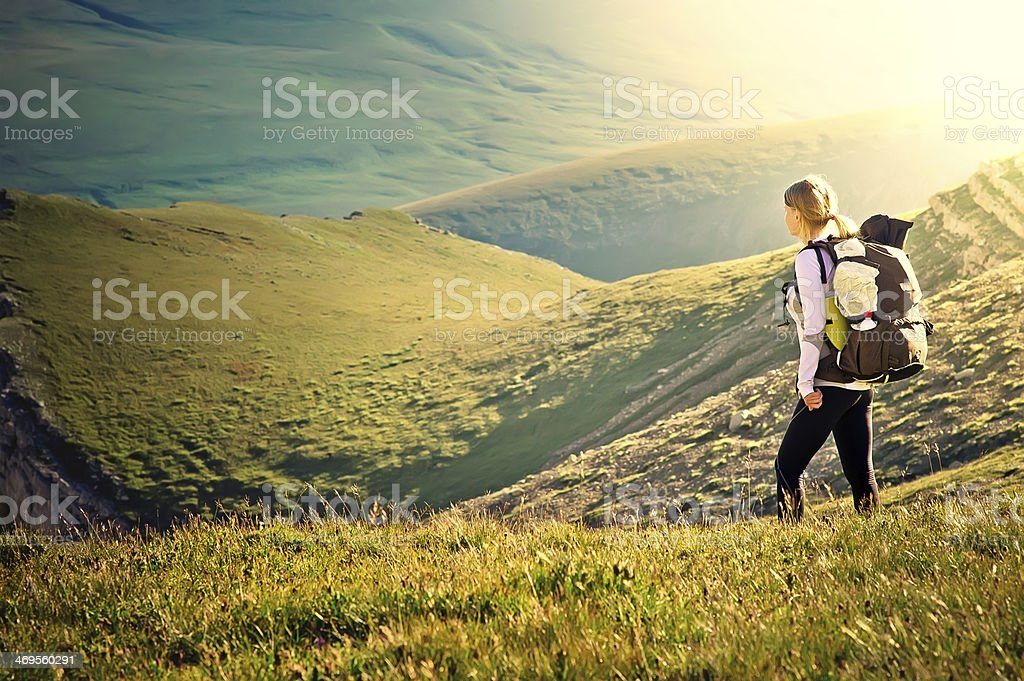 Woman Traveler with Backpack hiking in Mountains stock photo