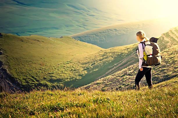 女性のお客様の山々でのハイキングのバックパック - 野生動物旅行 ストックフォトと画像