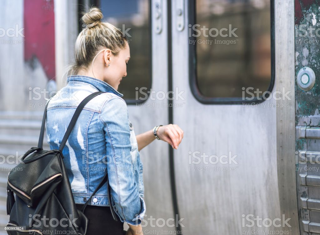 Woman traveler with backpack on rail station checking time royalty-free stock photo