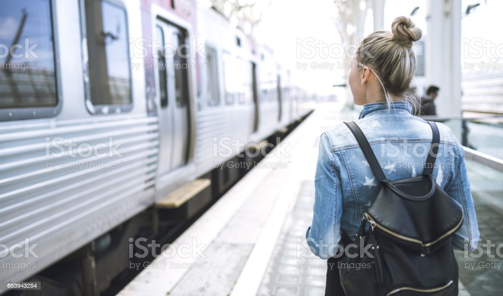 Woman traveler with backpack on rail station stock photo