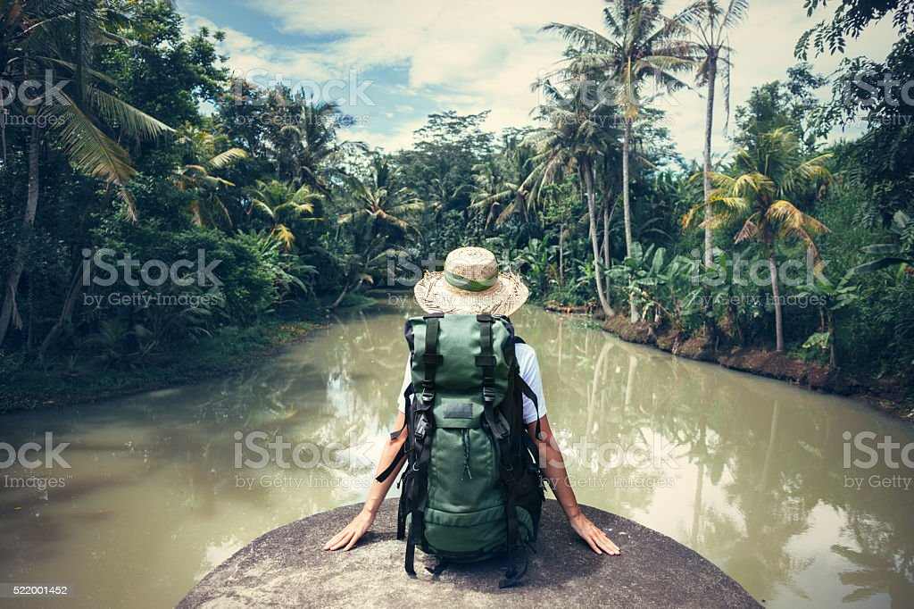 Woman traveler with backpack sitting on the edge stock photo