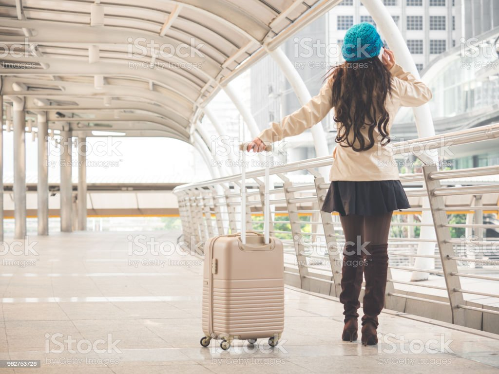 Woman traveler with bag, luggage, suitcase arrival at the airport during travel aboard - Foto stock royalty-free di A bordo