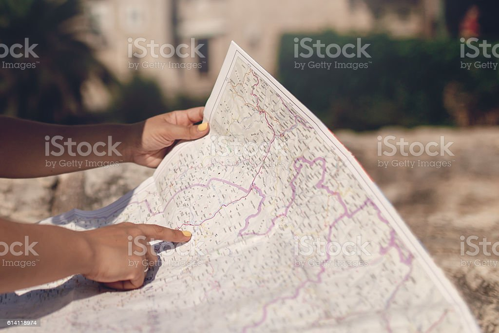 Woman traveler with map in old town at daytime stock photo