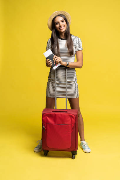 Woman traveler with suitcase on color background. stock photo