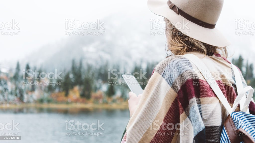 Woman traveling among mountains and using mobile phone, boho style stock photo