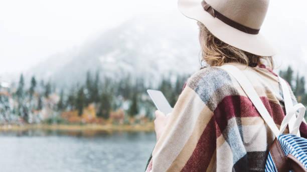 Woman traveling among mountains and using mobile phone, boho style stock photo